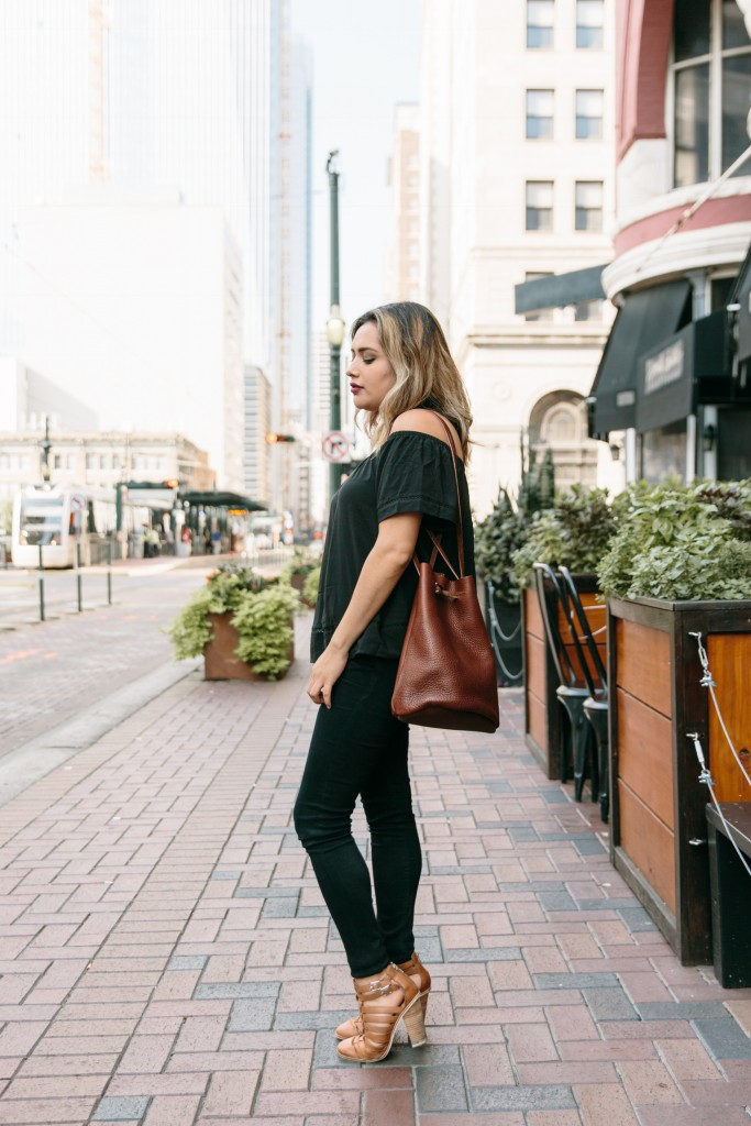 Black over the shoulder top with bucket bag